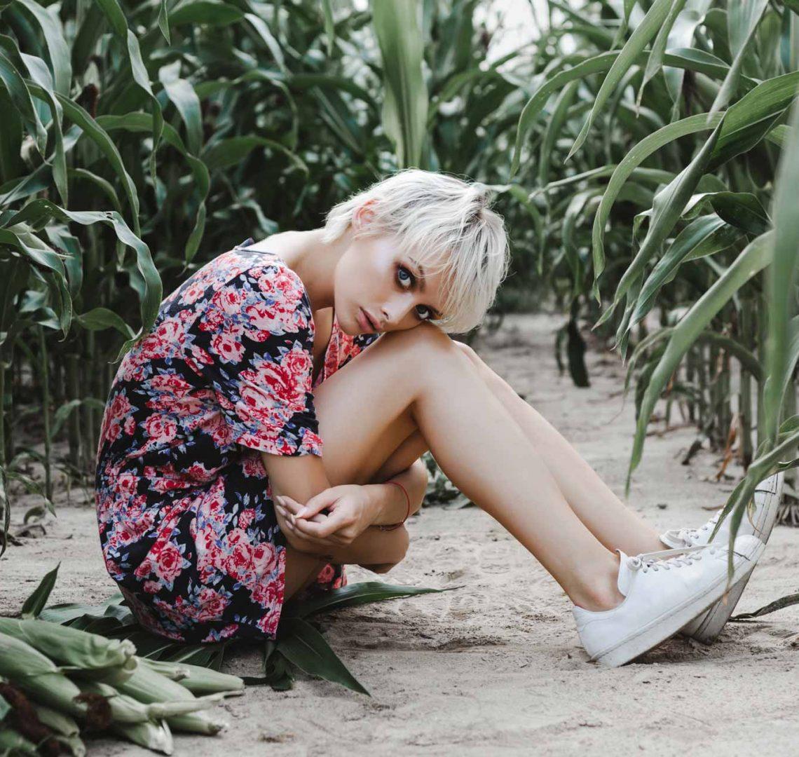 girl-between-green-leaves-in-a-corn-field-PD8U4Z5.jpg